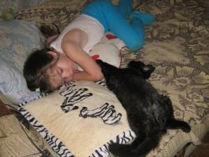 девочка и черный кот лежат вместе фото на диване